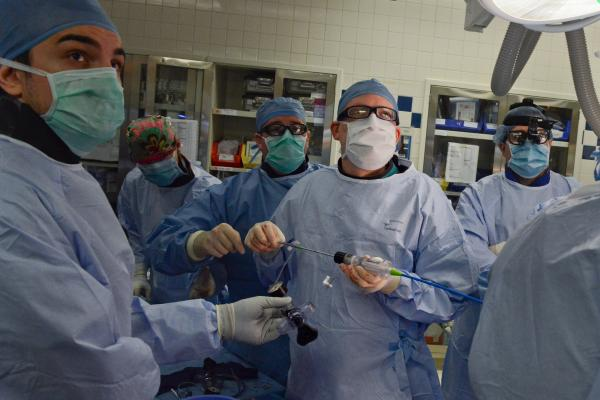 """Using the terms plumber, electrician, carpenter are easy for most patients to understand when explaining the rolls of specialists in complex cardiology procedures. In this image, interventional cardiologist """"plumbers"""" and a cardiac surgeon """"carpenter"""" work as part of the a structural heart team at Henry Ford Hospital while guiding the device using live echo images from the """"video guy."""""""