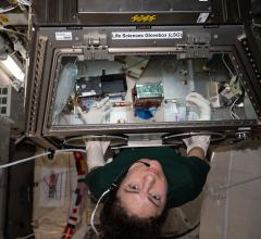 """Astronaut Jessica Meir """"feeds"""" a set of the University of Washington's engineered heart tissues (inside the green-topped case at center) riding aboard the International Space Station as part of a test of micro-gravity on heart health. Image courtesy of NASA."""