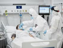 A COVID patient on a ventilator in an ICU. The clinicians are wearing larger photos of themselves to help build better relations with their patients and make it easier for fellow staff to see identify who they are under the PPE.