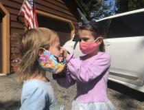 Vivian Fornell, 6,  adjusts the mask of her sister Katherine Fornell, 4, before going into a friends house for a visit in Hawthorn Woods, Illinois, near Chicago. Photo by Dave Fornell