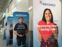 There are several reminders around the Abiomed headquarters office that the products employees there make are designed to help save lives. These are among many posters of actual patients who received Impella devices, which helped their survival.