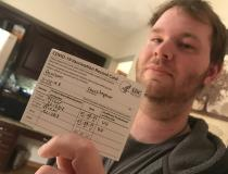 Iowa nursing home worker Christopher Davison shows off his COVID vaccine card. Since he works at a nursing home facility, he was among the first in line for the vaccine in December 2020 and January 2021. Photo by Dave Fornell