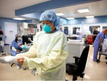 A Cedars-Sinai nurse dons personal protective equipment (PPE) before entering a COVID-19 patient's room. Nurses from various departments have been reassigned in large numbers to COVID wards to meet the demand in caring for this new patient populations at hospitals. Read the article Hundreds of Nurses Reassigned to Meet COVID-19 NeedsPhoto by Cedars-Sinai.