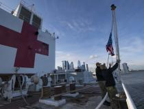 Sailors participate in a morning colors ceremony aboard the hospital ship USNS Comfort (T-AH 20) while the ship is moored in New York City in support of the nation's COVID-19 response efforts. Comfort was supposed to serve as a referral hospital for non-COVID-19 patients currently admitted to shore-based hospitals. However after criticism the ship treated very few patients it will be opened up to treat COVID-19 patients. U.S. Navy photo by Mass Communication Specialist 2nd Class Sara Eshleman