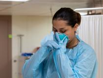 Hospitalman Pearl Alvarado, a native of San Antonio, dons a face mask aboard the hospital ship USNS Mercy (T-AH 19) before working with a patient. Mercy deployed in support of the nation's COVID-19 response efforts, and will serve as a referral hospital for non-COVID-19 patients currently admitted to shore-based hospitals. This allows shore base hospitals to focus their efforts on COVID-19 cases. U.S. Navy photo by Mass Communication Specialist 2nd Class Abigayle Lutz.